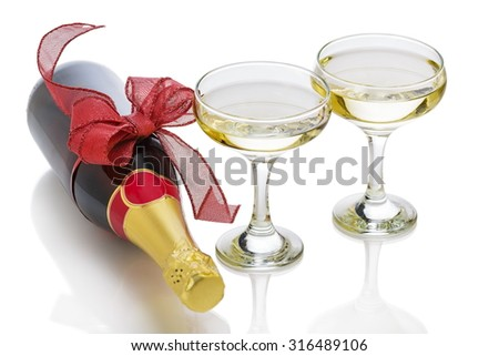 Festive champagne bottle with red bow knot and two glasses over white background.
