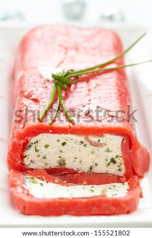 Festive cheese terrine wrapped with smoked red salmon - stock photo