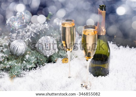 Festive Christmas and New Year champagne background with two glasses and a bottle of champagne in winter snow with silver decorations and a bokeh background of sparkling party lights - stock photo