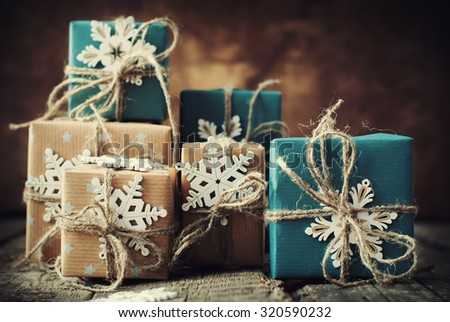 Festive Christmas Boxes Decorated in Beige, Blue Paper, Linen Cord and Snowflakes on Dark Wooden Table. Toned - stock photo