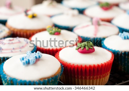Festive Christmas cup cakes colorfully decorated with white icing and topped sugar snowflakes, trees and gifts.  - stock photo