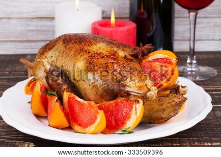 Festive Christmas duck baked with grapefruits and rosemary, glass of wine and candles