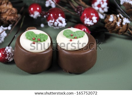 Festive Christmas food, plum pudding decorated chocolates in holiday green background with selective focus, close up. - stock photo