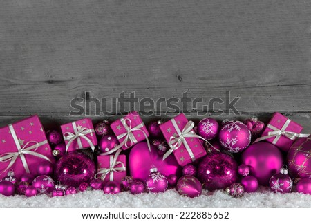 Festive christmas frame: wooden background with pink presents and balls. - stock photo