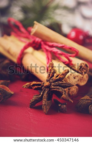 Festive Christmas spices and ingredients on dark red wood background for holiday baking and cooking concept with added filters and retro hand drawn style text.  - stock photo