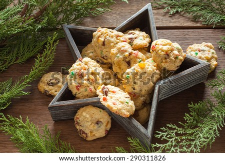 Festive Christmas still life  homemade shortcrust cookie with multicolored candied peel in wooden star plate with christmas green on wood background - stock photo