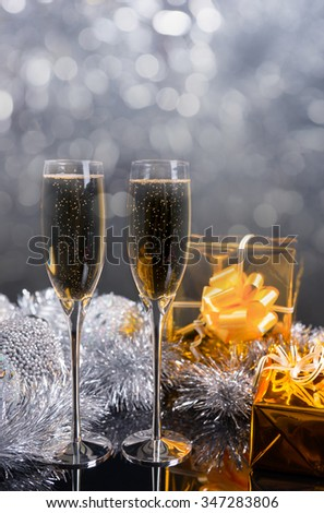 Festive Christmas Still Life with Copy Space - Pair of Glasses Filled with Sparkling Champagne, Gifts Wrapped in Gold Paper and Silver Decorations on Table