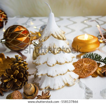 Festive Christmas table decoration with tree candle, balls and table lights