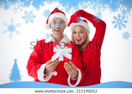 Festive couple smiling and holding gift against snow flake frame in blue - stock photo