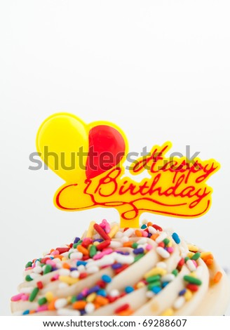 Festive Cupcake Topped with Colorful Sprinkles and Happy Birthday Sign on White Background - stock photo