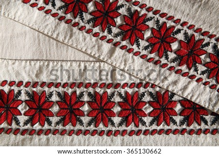 Festive / decorative linen towel from my grandmother's trunk, woven manually using domestic weaving loom and embroidered with red and black threads by original pattern. Traditional crafts. 1930s. - stock photo