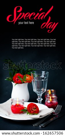 Festive dining table setting with red buttercup flowers, candles, napkins and shiny new cutlery on a black background - stock photo