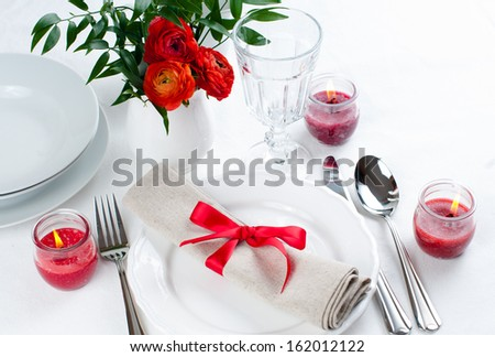 Festive dining table setting with red flowers, candles and ribbons in white tones - stock photo