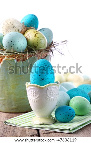 Festive easter scene with turquoise speckled egg in cup - stock photo