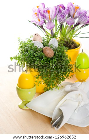 festive easter table setting with flowers, eggs and candles decoration on white background - stock photo
