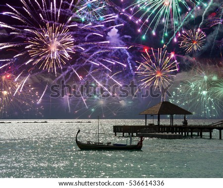 Festive fireworks over the sea and a boat silhouette on water. Maldives.