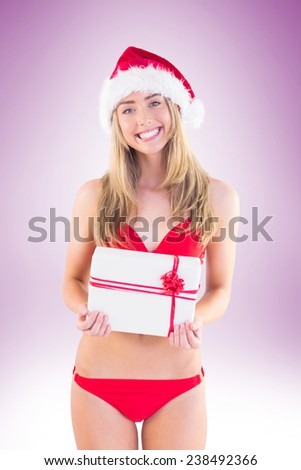 Festive fit blonde in red bikini showing gift on vignette background - stock photo