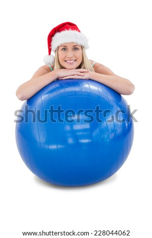 Festive fit blonde leaning on exercise ball on white background - stock photo