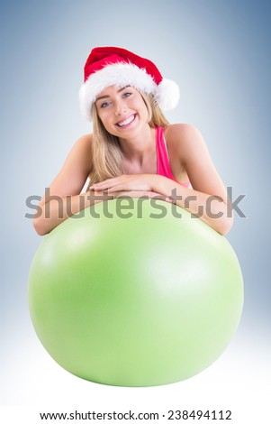 Festive fit blonde posing with exercise ball on vignette background - stock photo