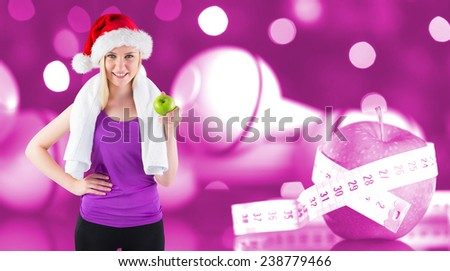 Festive fit blonde smiling at camera holding apple against pink - stock photo