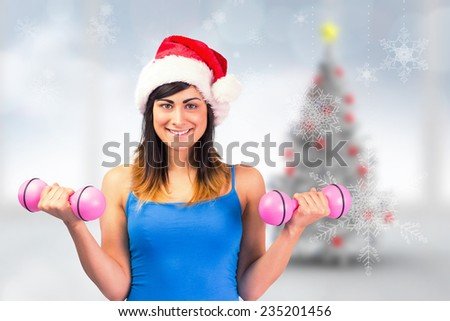 Festive fit brunette holding dumbbells against blurry christmas tree in room - stock photo