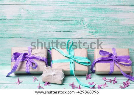 Festive gift boxes and  tender lilac flowers on turquoise wooden background. Selective focus. Place for text. - stock photo