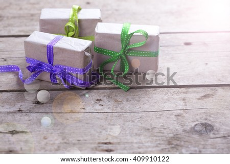 Festive gift boxes with presents  in ray of light on vintage wooden background. Selective focus. Place for text. - stock photo