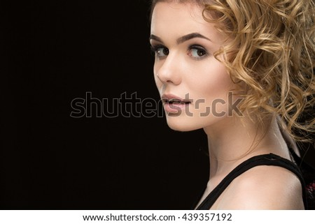 Festive girl. Cropped closeup of a young beautiful cheerful woman with professional curly hairstyle looking to the camera joyfully copyspace on the side - stock photo