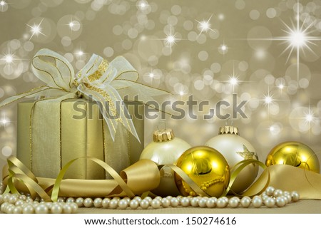 Festive gold christmas present with seasonal decorations.