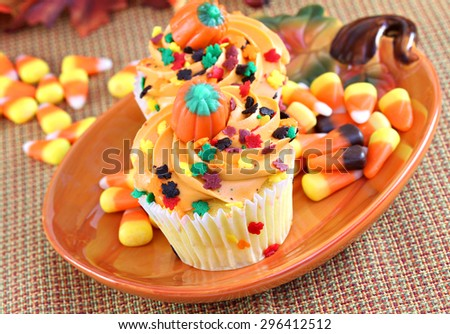 Festive Halloween cupcakes with sprinkles and holiday candy in a fall setting.