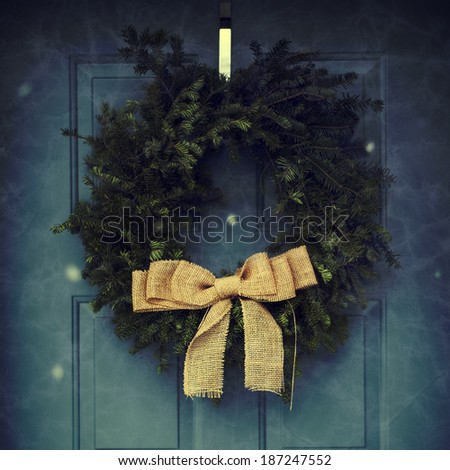 Festive holiday wreath hanging on a blue door, instagram filter style - stock photo