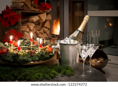 festive interior decoration for christmas and new year with bottle of champagne and fireplace. candlelight dinner - stock photo