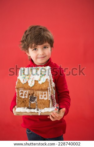 Festive little boy holding gingerbread house on red background - stock photo