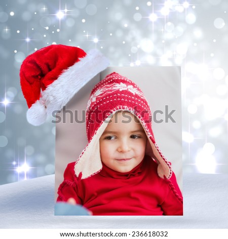 Festive little boy on the couch against light design shimmering on silver