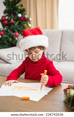 Festive little boy writing wish list at home in the living room - stock photo