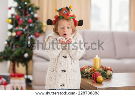 Festive little girl blowing over hands at home in the living room