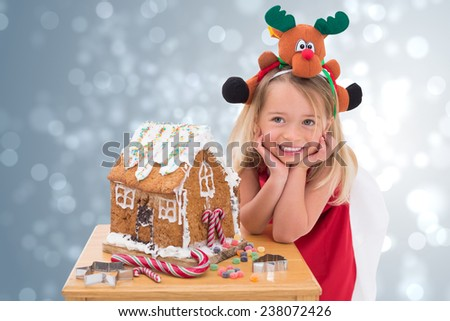 Festive little girl making gingerbread house against light design shimmering on silver - stock photo
