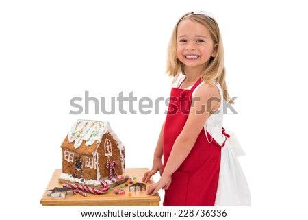 Festive little girl making gingerbread house on white background - stock photo