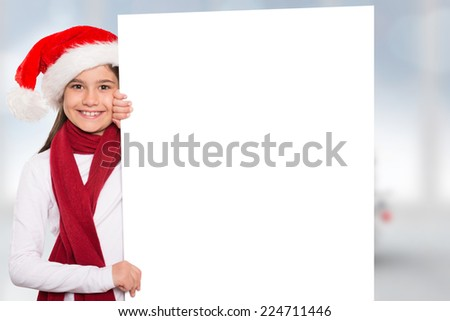 Festive little girl showing card against blurry christmas tree in room - stock photo