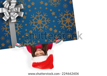 Festive little girl showing card against christmas wrapping paper with bow - stock photo