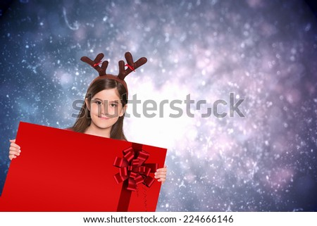 Festive little girl showing card against red christmas ribbon - stock photo