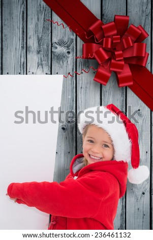 Festive little girl showing poster against wood with festive bow - stock photo