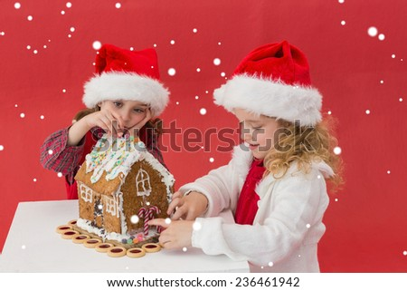 Festive little girls making a gingerbread house against snow - stock photo