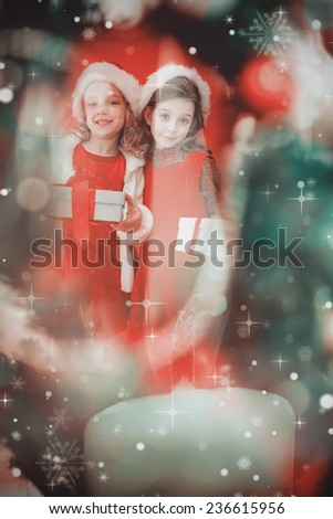 Festive little girls smiling at camera with gifts against candle burning against festive background - stock photo