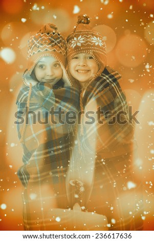 Festive little girls under a blanket against candle burning against festive background - stock photo
