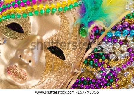 Festive Mardi Gras beads and a golden mask - stock photo