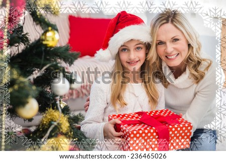 Festive mother and daughter beside christmas tree against snowflake frame - stock photo