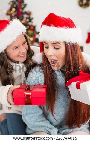 Festive mother and daughter exchanging gifts at home in the living room - stock photo