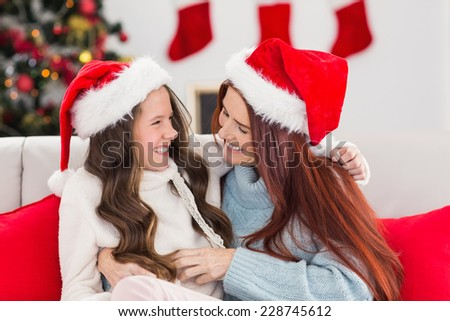 Festive mother and daughter on the couch at home in the living room - stock photo