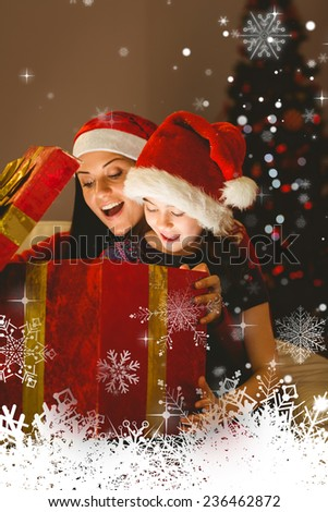 Festive mother and daughter opening a christmas gift against snowflakes - stock photo